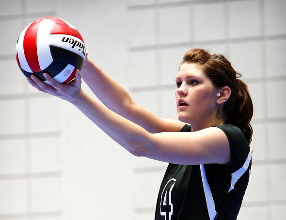 Девушка держит мяч и целится для верхней подачи. Обратите внимание на руки и высоту для подброса мяча.